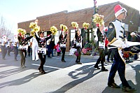 Teens marching and playing their instruments in a parade.