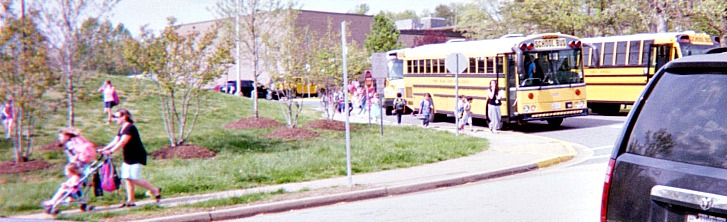 Kids lining up to board the bus after school.