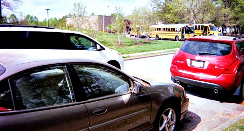 Parents in cars waiting to take their children home after school.
